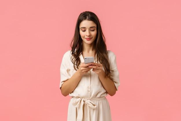 Романтичная милая, красивая молодая женщина в платье, беседует с парнем, улыбается, держит смартфон и нажимает на экран, чтобы заказать онлайн, делать покупки с помощью приложения Premium Фотографии