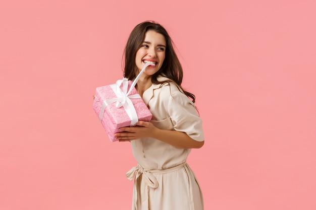 Беззаботная, веселая и веселая молодая девушка, вечеринки, чудесный день рождения, кусающий узелок на милом подарке Premium Фотографии
