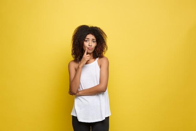 美しい魅力的なアフリカ系アメリカ人の女性は、彼女の縮毛アフロの髪を再生する投稿します。黄色のスタジオの背景。スペースをコピーします。 無料写真