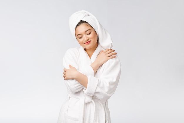 Спа по уходу за кожей красоты азиатская женщина сушит волосы полотенцем на голове после душевой процедуры красивая многорасовая молодая девушка трогает мягкую кожу Premium Фотографии