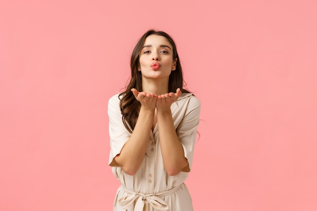 Посылаю любовь и заботу. очаровательная милая и нежная европейская брюнетка с вьющимися волосами, в весеннем платье, опираясь руками на сложенные губы, дует воздушный поцелуй с любовью, стоящая розовая стена Premium Фотографии