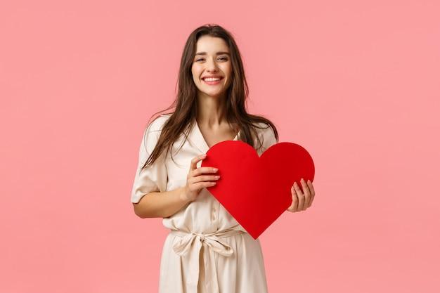 愚かな、のんきな、素敵な魅力的なデザインの凝った服のブルネットの少女、赤い大きなハートのカードを持っている、これまでで最高のバレンタインデーを持っている、笑顔で笑って喜んでいる、明るいピンクの壁に立っている Premium写真