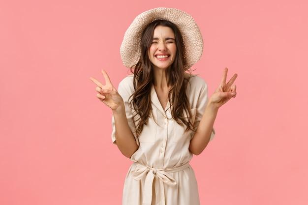 幸福、応援、喜びのコンセプトです。愚かな格好良い、帽子とドレスの女性らしいガールフレンド、平和の兆しを見せ、のんきな笑い、休暇を楽しんでいる、旅行中、ピンクの壁 Premium写真