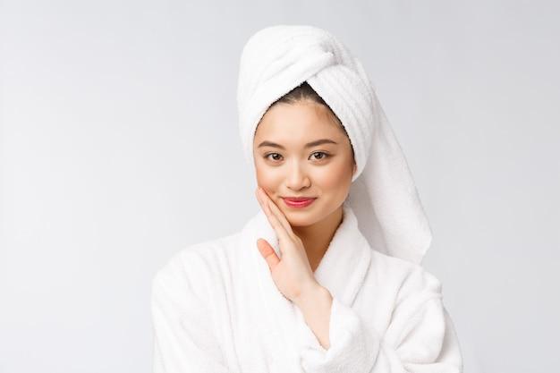 Спа по уходу за кожей красоты азиатская женщина сушки волос полотенцем на голове после душа. красивая многорасовых молодая девушка, касаясь мягкой кожи. Premium Фотографии