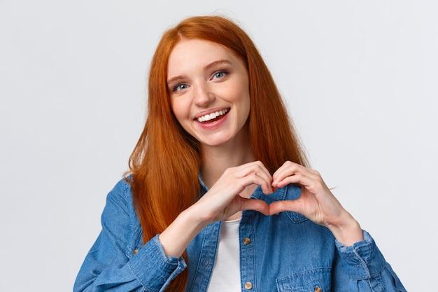 幸せなバレンタインデー、愛。キュートで優しいロマンチックな赤毛のガールフレンドがハートのサインを示し、共感を告白し、情熱を表明するなど、素晴らしいアートワークを鑑賞し、感謝し、白い壁に立つ Premium写真