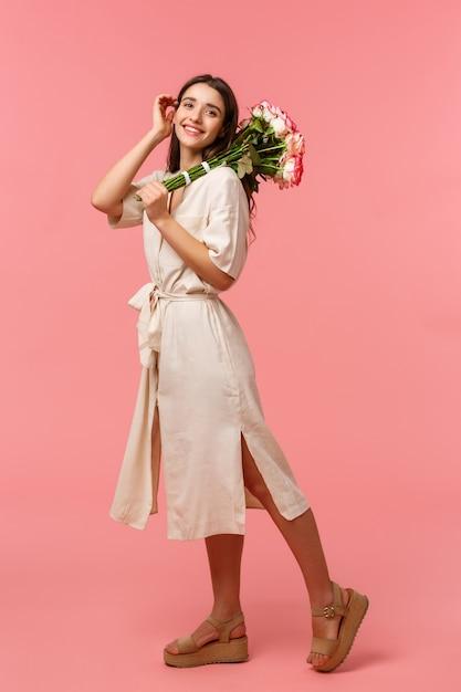 フルレングスの縦長の肖像画、デートを楽しむ夢のようなロマンチックなブルネットの女性、花束のバラを保持、優しく髪に触れる、愚かな笑顔、花を受け取る、立っているピンクの壁 Premium写真