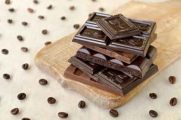 Грубые кусочки шоколада на деревянной доске, кофейные зерна разбросаны по всему Premium Фотографии