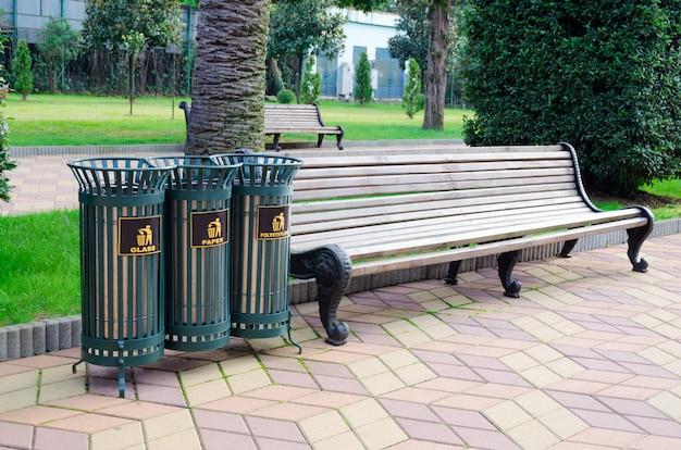 Мусорные железные решетчатые бункеры для сортировки мусора в городском парке рядом со скамейкой. Premium Фотографии