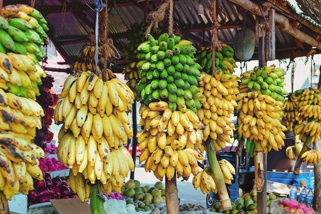 スリランカ通りにあるフルーツショップには、さまざまな製品とバナナの大きな枝があります。アジアの農産物。 Premium写真