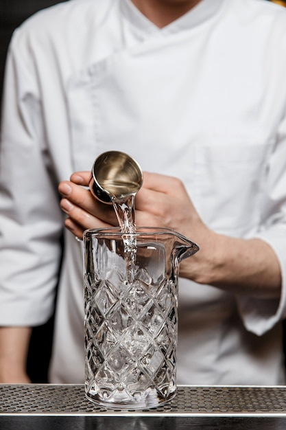 バーでカクテルを事前に準備し、ジガーを使用して混合グラスにアルコールを追加するバーテンダー Premium写真