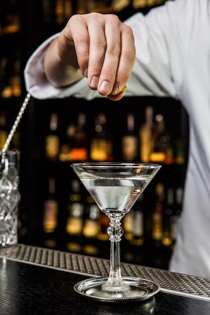 バーでカクテルを準備しているバーテンダー、マティーニグラスの飲み物にレモンの皮を絞る Premium写真