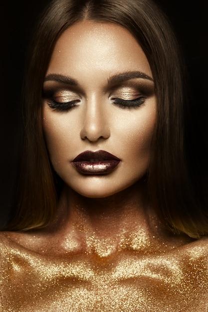 彼女の顔にゴールドラメを持つ美しい少女 Premium写真