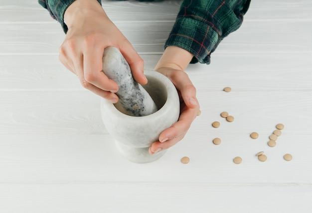 カップで丸薬を粉砕する人 Premium写真