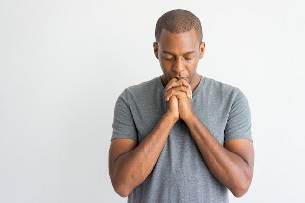 閉じた目で祈っている静かな精神的なハンサムなアフリカの男。 無料写真