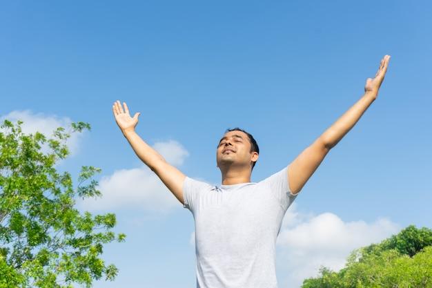 インド人、青空と緑の木の枝で野外で集中して手を上げる 無料写真