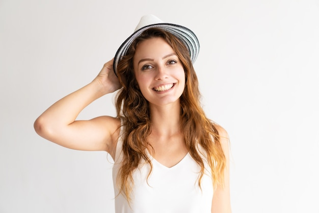 幸せな若い女性モデルの肖像画は、カメラを見て、笑顔で、帽子でポーズを取る。 無料写真