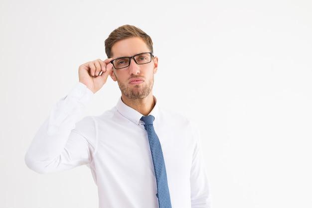 傲慢なビジネスマン眼鏡を調整し、カメラを見て 無料写真