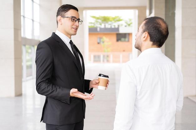 オフィスコリドールでクライアントに話す自信を持っている若いコンサルタント 無料写真