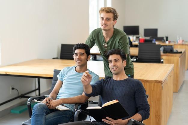 Любопытные студенты смотрят презентацию и обсуждают ее Бесплатные Фотографии