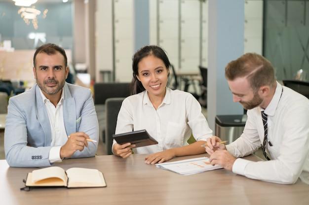 オフィスでダイアグラムを扱うポジティブなビジネスマン 無料写真