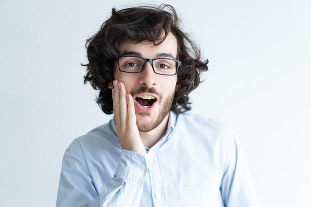 彼の口を開いて頬に触れているショッキングな黒髪の男 無料写真