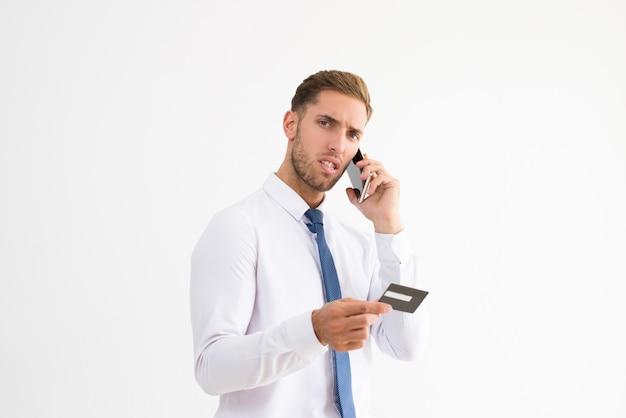 クレジットカードを持って話している心配しているビジネスマン 無料写真