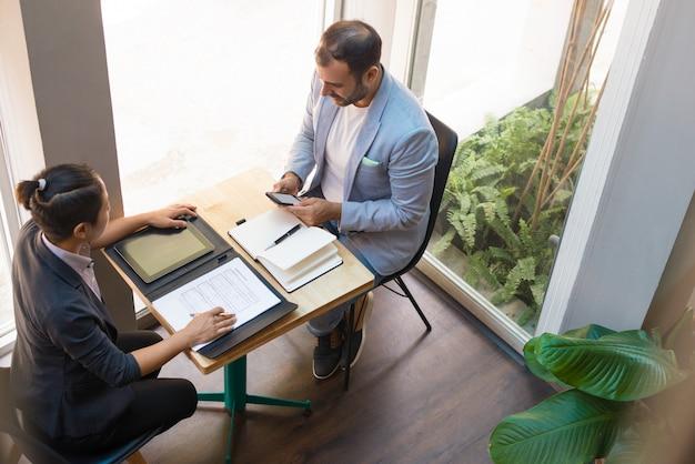 カフェでミーティングを持つ深刻なビジネスパートナーの視点から 無料写真