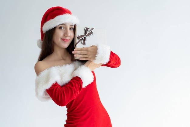サンタの帽子の陽気な少女は、クリスマスプレゼントを受け取ることを喜んで 無料写真