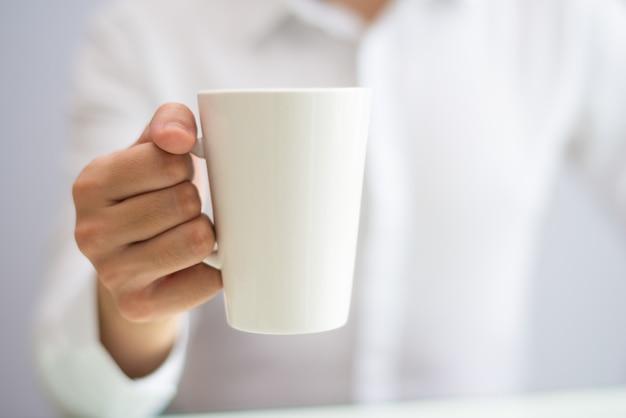マグカップからのオフィスの従業員の飲み物のコーヒーのクローズアップ 無料写真