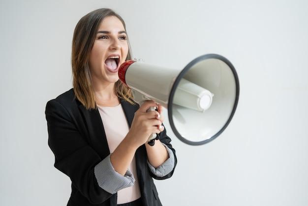 Уверенная молодая кавказская женщина кричит в сторону в мегафон Бесплатные Фотографии