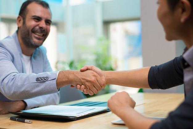 Возбужденный латиноамериканский работодатель поздравляет нового сотрудника Бесплатные Фотографии