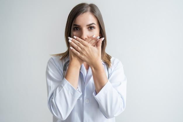 ショックを受けた女性の白人の専門家が口を覆うラボコート 無料写真