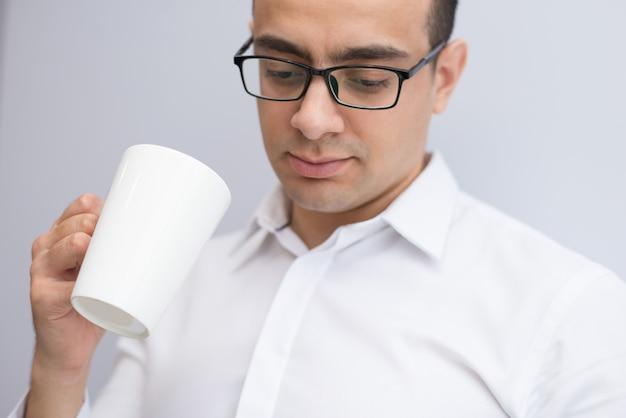 コーヒーを飲みながらメガネで集中している実業家のクローズアップ 無料写真