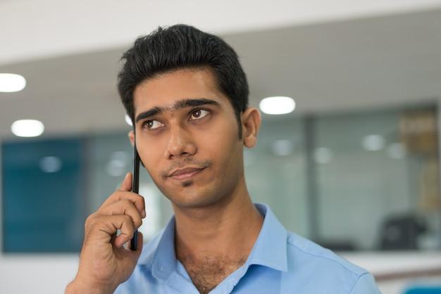 携帯電話で顧客に聞いて物思いにふけるハンサムな男 無料写真