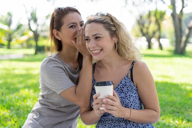 Женщина шепчет секрет улыбающейся девушке в парке Бесплатные Фотографии