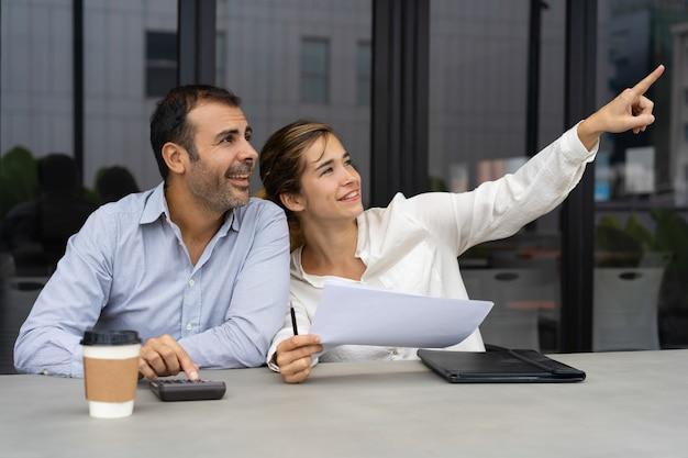 不動産投資を議論する陽気なビジネスパートナー 無料写真