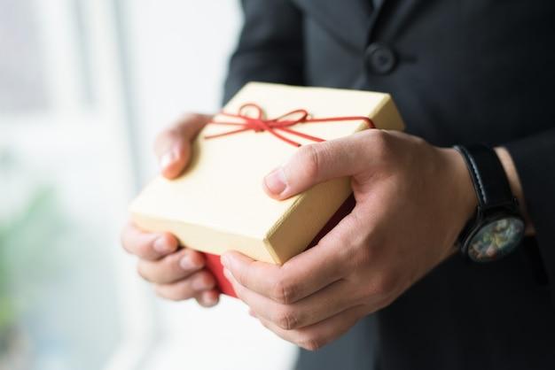 ギフト用の箱を保持している腕時計を持ったビジネスマンのクローズアップ 無料写真