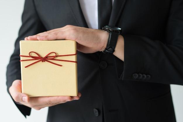 Крупный план человека с наручными часами, держащего подарочную коробку Бесплатные Фотографии