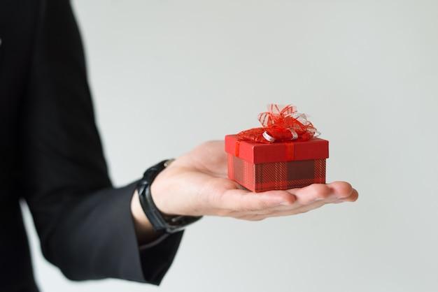 Крупный план до неузнаваемости человека, держащего небольшой подарок на ладони Бесплатные Фотографии