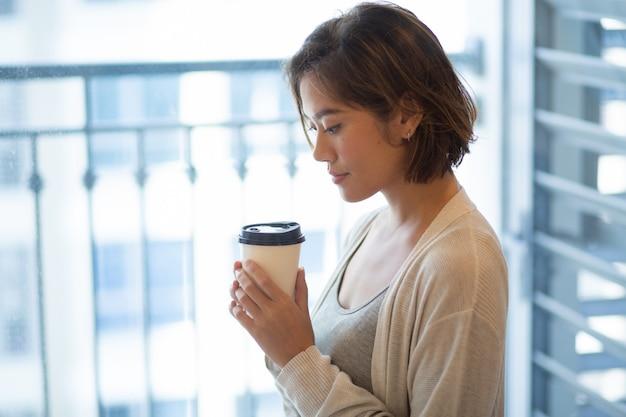 コーヒーカップと立っている穏やかな若い女性の肖像画 無料写真