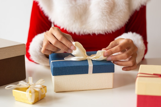 プレゼントボックスの上にリボンを結ぶ女 無料写真