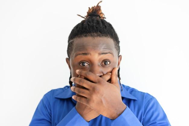 Потрясенный темнокожий мужчина, покрывающий рот обеими руками Бесплатные Фотографии