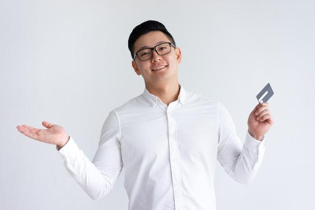 クレジットカードを押しながら手を投げて笑顔のアジア人男性 無料写真