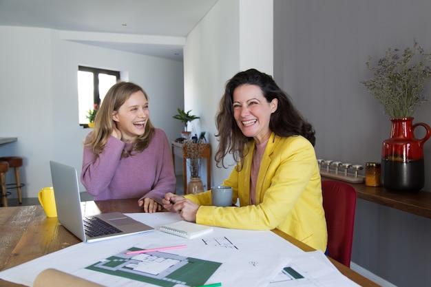 図面を扱うと笑っている女性建築家 無料写真