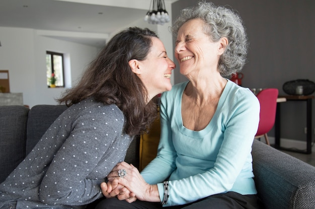 幸せな老婦人と彼女の娘が笑っていると手を繋いでいます。 無料写真