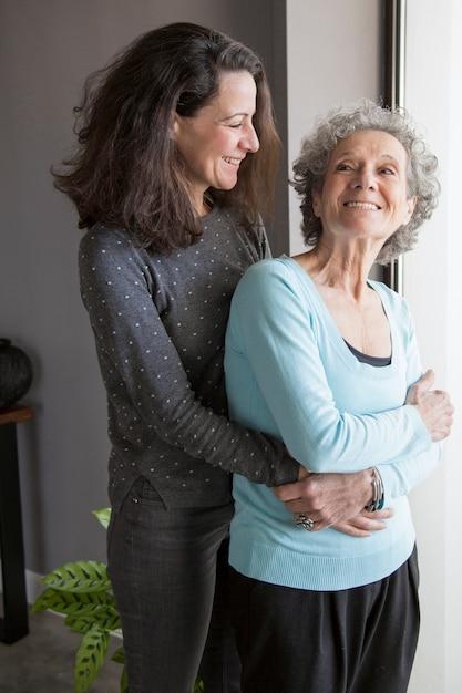 Веселая взволнованная старшая женщина обняла дочь, возвращаясь Бесплатные Фотографии