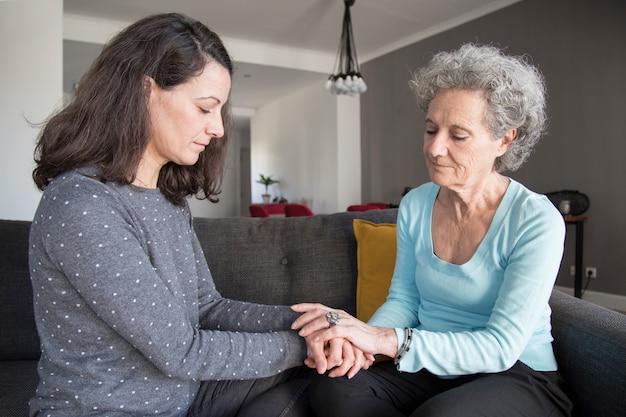 深刻な年配の女性と彼女の娘が手を繋いでいます。 無料写真