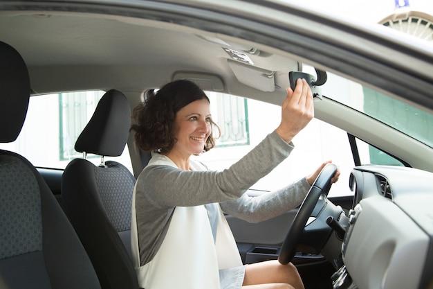 鏡で見ている陽気な女性の車の運転手 無料写真