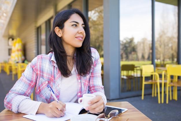 夢のような女性が屋外カフェでメモを作る 無料写真