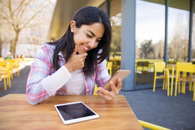 タブレットとスマートフォンを使用して屋外カフェで笑顔の女性 無料写真